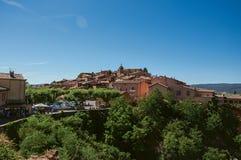 Vista panorâmica da vila de Roussillon e de madeiras circunvizinhas foto de stock