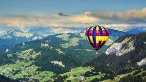 Vista panorâmica das montanhas com um balão de ar quente Foto de Stock Royalty Free