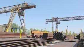 Vista panorâmica de um grande armazém com metal, uma vista panorâmica de um armazém com um guindaste de pórtico e um trem de merc vídeos de arquivo