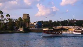 Vista panorâmica do arco de Universal Studios, da esfera do mundo, das palmeiras e do barco do táxi em Citywalk na área de Univer vídeos de arquivo