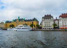 Vista panorâmica do barco ao cais com barcos e as construções bonitas de Stromkajen fotos de stock
