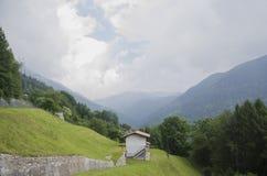 Vista panorâmica do cenário alpino idílico da montanha com casa italiana e os prados verdes frescos no tempo nebuloso bonito imagem de stock