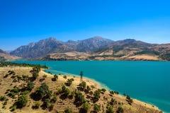 Vista panorâmica do lago Charvak, um lago-reservatório artificial enorme criado erigindo uma represa de pedra alta no rio de Chir Imagens de Stock