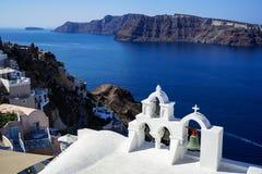 Vista panorâmica do Mar Egeu e do caldera azuis bonitos da vila de Oia com primeiro plano branco da igreja, construções ao longo  Fotografia de Stock Royalty Free