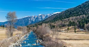 Vista panorâmica do rio de Noce cercada por cumes italianos neve-tampados Dolomities das montanhas imagem de stock