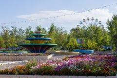 A vista panorâmica na zona do jogo e do resto no parque da cidade, chamou Kio Grandes fonte, roda, bandeiras, flores e campo de j fotos de stock