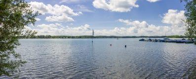 Vista panorâmica no lago bonito Wörthsee tomado do beira-mar paisagem Verde-azul com bandeira, barcos, cais e plantas na fotografia de stock