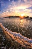 Vista panorâmica no mar do por do sol, na praia da areia, nas ondas e em guarda-chuvas cobridos com sapê na lente do peixe-olho Fotografia de Stock Royalty Free