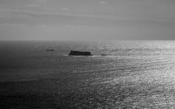 Vista panoramica ad alto contrasto sull'isola maltese Filfla con una nave del trasporto nel vicino Chiaro mare sull'orizzonte fotografia stock libera da diritti