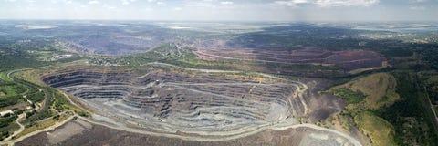 Vista panoramica aerea della cava di estrazione a cielo aperto con i lotti di macchinario sul lavoro immagini stock