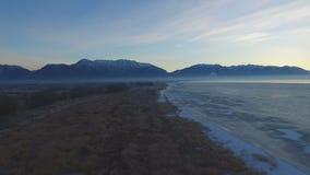 Vista panoramica aerea di un lago congelato e poi lungo il litorale con le montagne snowcapped oltre la nebbia e la foschia stock footage