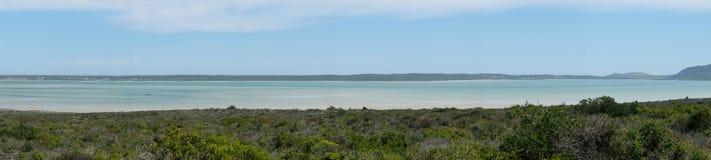 Vista panoramica che trascura un campo di Fynbos con una laguna ed i cieli blu nei precedenti Immagine Stock Libera da Diritti