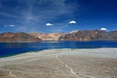 Vista panoramica del lago Pangong: nella priorità alta c'è un mucchio enorme della sabbia leggera, la strada attraverso cui le au Fotografia Stock Libera da Diritti