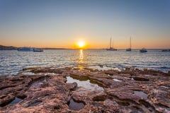 Vista panoramica del tramonto scenico alla linea costiera rocciosa dell'isola di Ibiza con le barche fotografia stock
