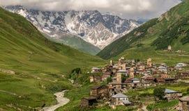 Vista panoramica del villaggio Usghuli con le vecchie torri di pietra sotto il più alta montagna georgiana Shkhara Fotografia Stock