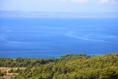 Vista panoramica della barca nell'oceano e nelle montagne nei precedenti e della foresta di conifere verde nella priorità alta Fotografia Stock