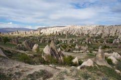 Vista panoramica della valle con molte formazioni rocciose bizzarre vicino al villaggio di Goreme fotografia stock libera da diritti
