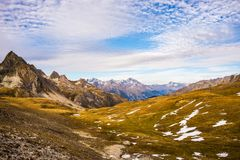 Vista panoramica della valle e catena montuosa in autunno variopinto con i prati gialli e picchi di alta montagna nei precedenti  Immagine Stock