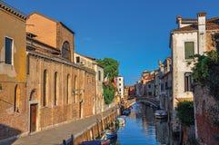 Vista panoramica delle costruzioni, del ponte e delle barche davanti ad un canale al tramonto a Venezia Immagini Stock Libere da Diritti