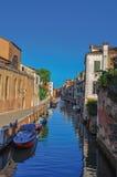 Vista panoramica delle costruzioni, del ponte e delle barche davanti ad un canale al tramonto a Venezia Fotografia Stock Libera da Diritti