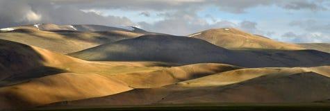 Vista panoramica delle gamme di alta montagna al tramonto: colline marroni con i pendii regolari arrotondati, ombre alternanti, t Fotografia Stock Libera da Diritti