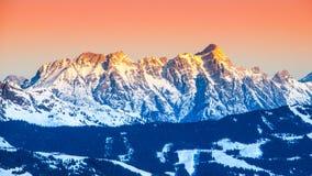Vista panoramica delle montagne di inverno Picchi alpini coperti da neve e illuminati dal sol levante Fotografie Stock