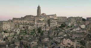Vista panoramica delle pietre e della chiesa tipiche di Matera sotto il cielo di tramonto