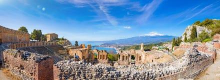 Vista panoramica delle rovine del teatro del greco antico in Taormina su fondo di Etna Volcano, Italia immagini stock