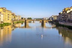 Vista panoramica di Arno River e del ponte medievale di pietra Ponte Vecchio con la bella riflessione delle case variopinte, picc immagini stock
