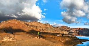 Vista panoramica di bello paesaggio geotermico con la donna che sta sulla montagna superiore vicino al lago del cratere di Askja,  Immagini Stock