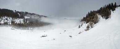 Vista panoramica giù una valle della montagna con le nuvole basse e il overca Fotografia Stock Libera da Diritti
