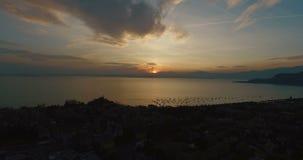 Vista panoramica meravigliosa sul tramonto sopra la bella polizia del lago (Lago di Garda) con le montagne, gli yacht e i sailing stock footage