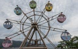Vista panoramica su grande Ferris Wheel con il giro, cabine variopinte con gli animali stampati Situato nella terra di vista di A fotografia stock