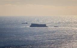 Vista panoramica sull'isola maltese Filfla con una nave del trasporto nel vicino Chiaro mare sull'orizzonte fotografia stock libera da diritti
