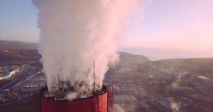Vista panoramica vicina cima di camino della centrale elettrica e del riscaldamento centrale con vapore stock footage