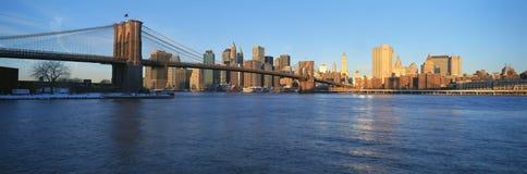 Vista panorámica del puente de Brooklyn y de East River en la salida del sol con New York City, en donde las torres del comercio  Fotos de archivo libres de regalías