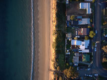 Vista para baixo com uma opinião de olho de pássaros da praia e das casas Fotos de Stock Royalty Free