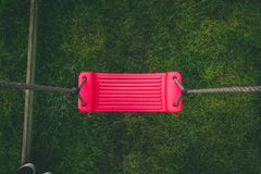 Vista para baixo em um balanço abandonado vermelho no jardim imagens de stock royalty free