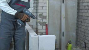 Vista parcial da braçadeira de junta da fixação do construtor aos blocos com broca elétrica video estoque