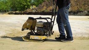 Vista parcial de la arena de presi?n del hombre con el vibrador superficial de la placa en hoyo de la fundaci?n almacen de metraje de vídeo