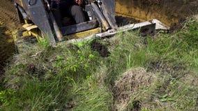 Vista parcial de la niveladora que quita capa de suelo herboso durante trabajos de la tierra almacen de video