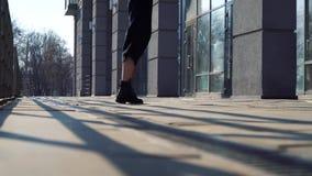 Vista parcial de las piernas de la mujer que bailan en la calle de la ciudad en rayos de la puesta del sol almacen de video