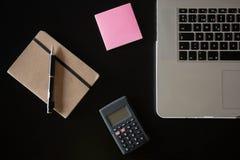 Vista parcial de um teclado de prata de um portátil com uma calculadora, umas notas de post-it cor-de-rosa e um caderno com um lá fotografia de stock