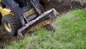 Vista parcial del mini cargador que quita capa de suelo herboso en los trabajos de la tierra almacen de metraje de vídeo