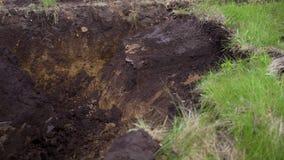Vista parcial do mini carregador que remove a camada de solo gramíneo durante trabalhos da terra filme