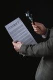 Vista parziale del contratto della lettura dell'uomo d'affari tramite la lente d'ingrandimento Fotografie Stock Libere da Diritti