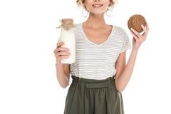 vista parziale della noce di cocco e del latte di cocco sorridenti della tenuta della donna in mani Fotografia Stock Libera da Diritti