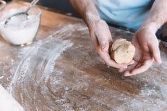 Vista parziale della pasta d'impastamento dell'uomo alla tavola di legno Fotografia Stock