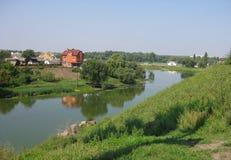 Vista per acquietare villaggio con le case sopra un fiume tranquillo fotografie stock libere da diritti
