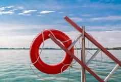 Vista piacevole dell'attrezzatura della salvavita contro il lago tranquillo del turchese ed il bello cielo blu Immagine Stock